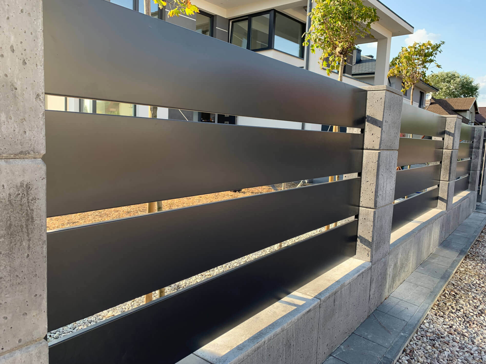 Nowoczesne ogrodzenie z przęsłami aluminiowymi i słupkami z pustaka gładkiego