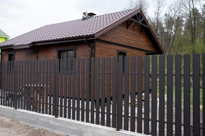 Płot sztachetowy zaluminium wkolorze brązowym imitującym drewno.