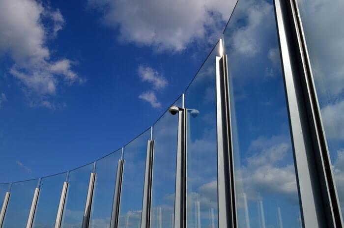 Szklane półkoliste ogrodzenie osadzone wmetalowych, srebrnych ramach